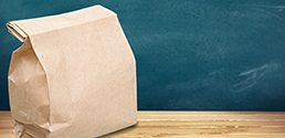 brown paper bag sitting on a desk in a classroom