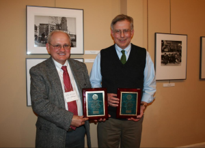 Picture of two men, Dr. Brown and Dr. Steponaitis, each holding an award plaque, smiling.