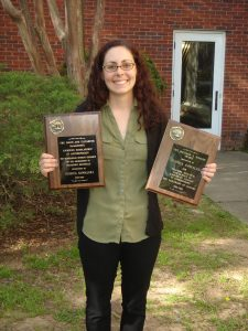 Jessica Kowalski holding the DeJarnette Scholarship and the Richard A. Krause Award at Graduate Honor's Day 4-4-16.