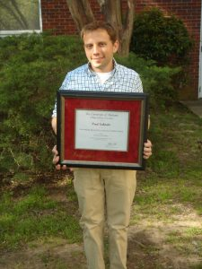 Paul Eubanks holding the A&S Outstanding Research by a Doctoral Student Award at Graduate Honor's Day 4-4-16.