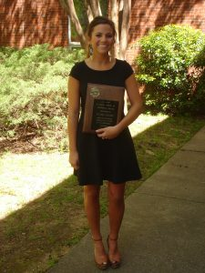 Taylor Lawhon holding C. Earl Smith Award at Undergraduate Honor's Day 4-8-16.