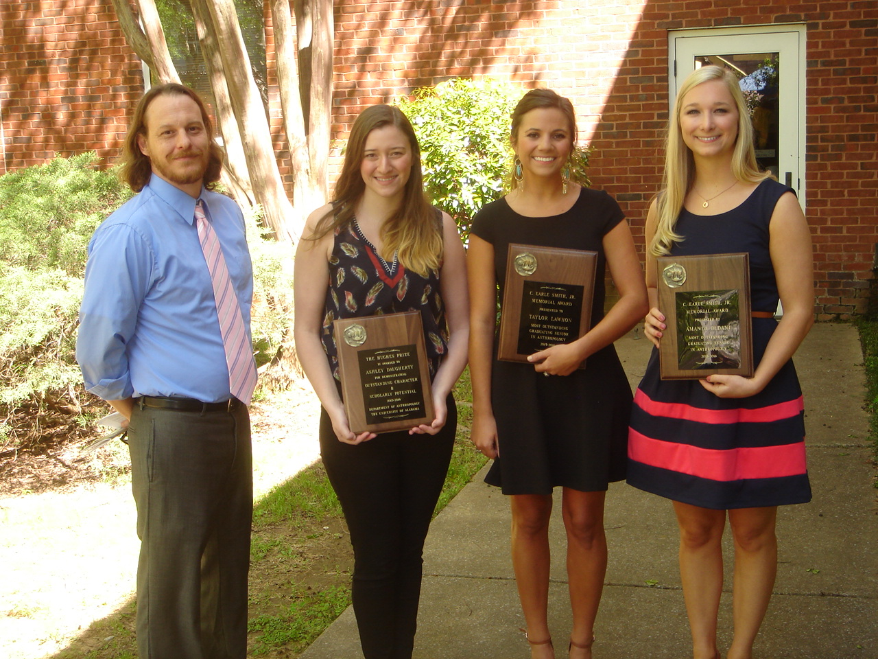 one professor and three young women; the women are holding plaques