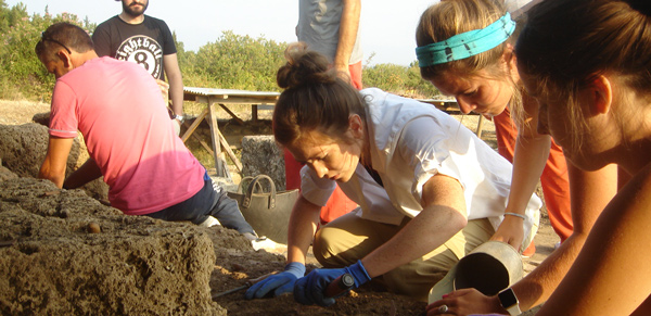 a group of students digging at an archaeological site