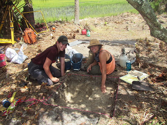 two students digging at a site