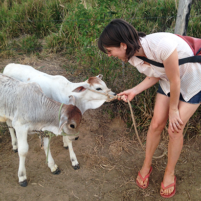 a young woman talking to a goat